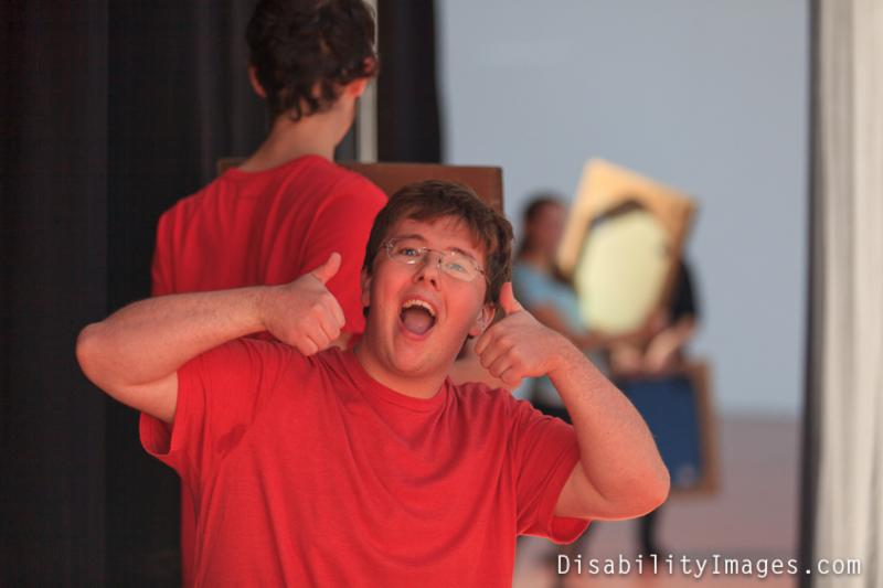 Young performer in red shirt smiling and giving two thumbs up with another performer in the backgound facing away from the camera