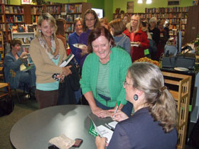Author Kathleen Ernst signing books at Heritage of Darkness launch party.