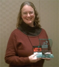 Author Kathleen Ernst holding the 2013 LOVEY Best Tradional Mystery Award she won for