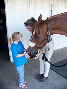 girl and instructor feeding horse
