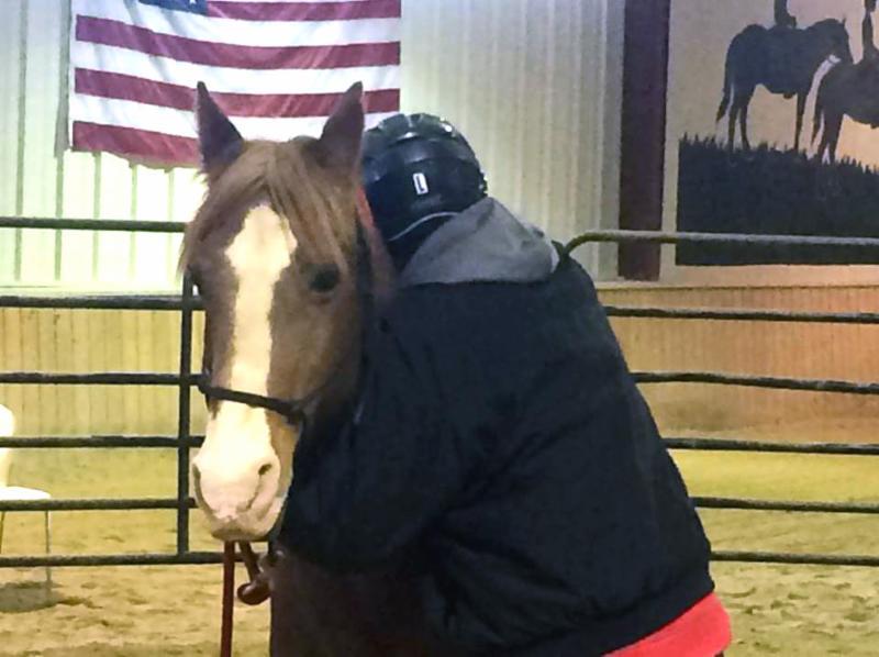 volunteer hugging a horse