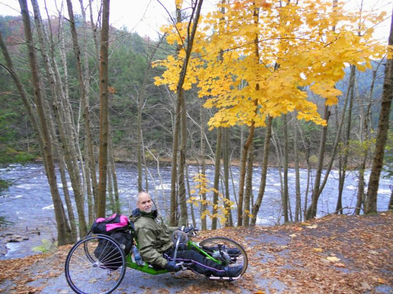 Rich on his handcycle by a stream in the mountains