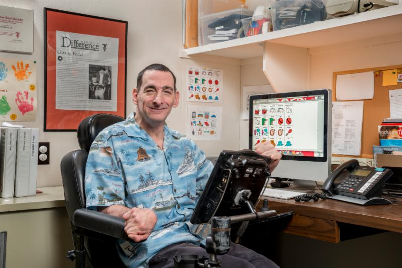 George smiles with his AAC in his office