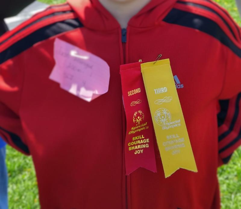 A close-up of a child_s torso displaying two ribbons _red and yellow_ won at the Special Olympics.