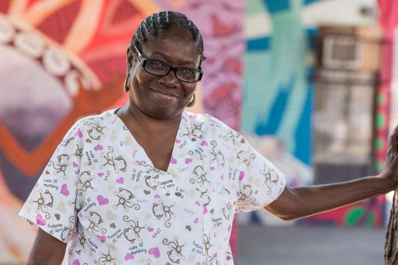 Linda smiles in front of a mural near her home in Philadelphia.