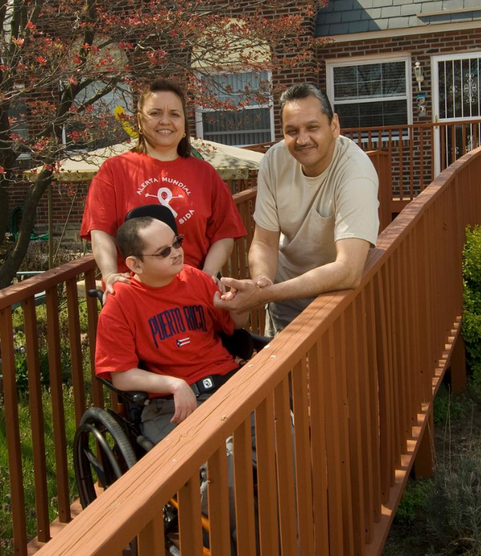 Joel and his parents stand on their ramp outside their home.