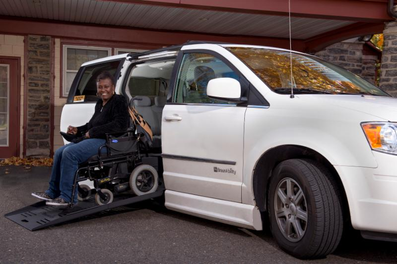 LaTrice smiles as she rides down the ramp on her new adapted van.