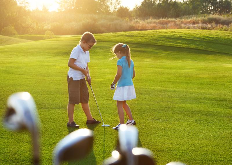 Casual kids at a golf field holding golf clubs. Sunset     Note  Visible grain at 100 , best at smaller sizes