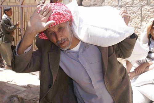 A Yemeni man carries food from an ICRC/Yemen Red Crescent distribution