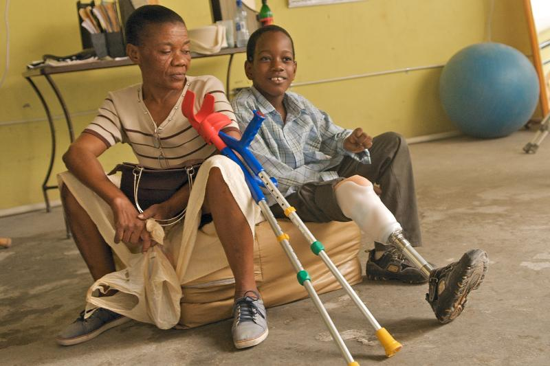 Jordanie (right), 10, and his aunt Eloude (left) rest for a minute at HHHI's temporary orthopedic clinic where Jordanie received a prosthesis and is given proper follow-up care.