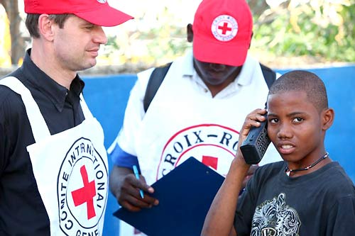 A boy affected by the earthquake uses an ICRC satellite phone to reassure his relatives.