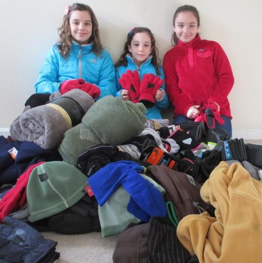Three young girls amid a large pile of winter clothing.