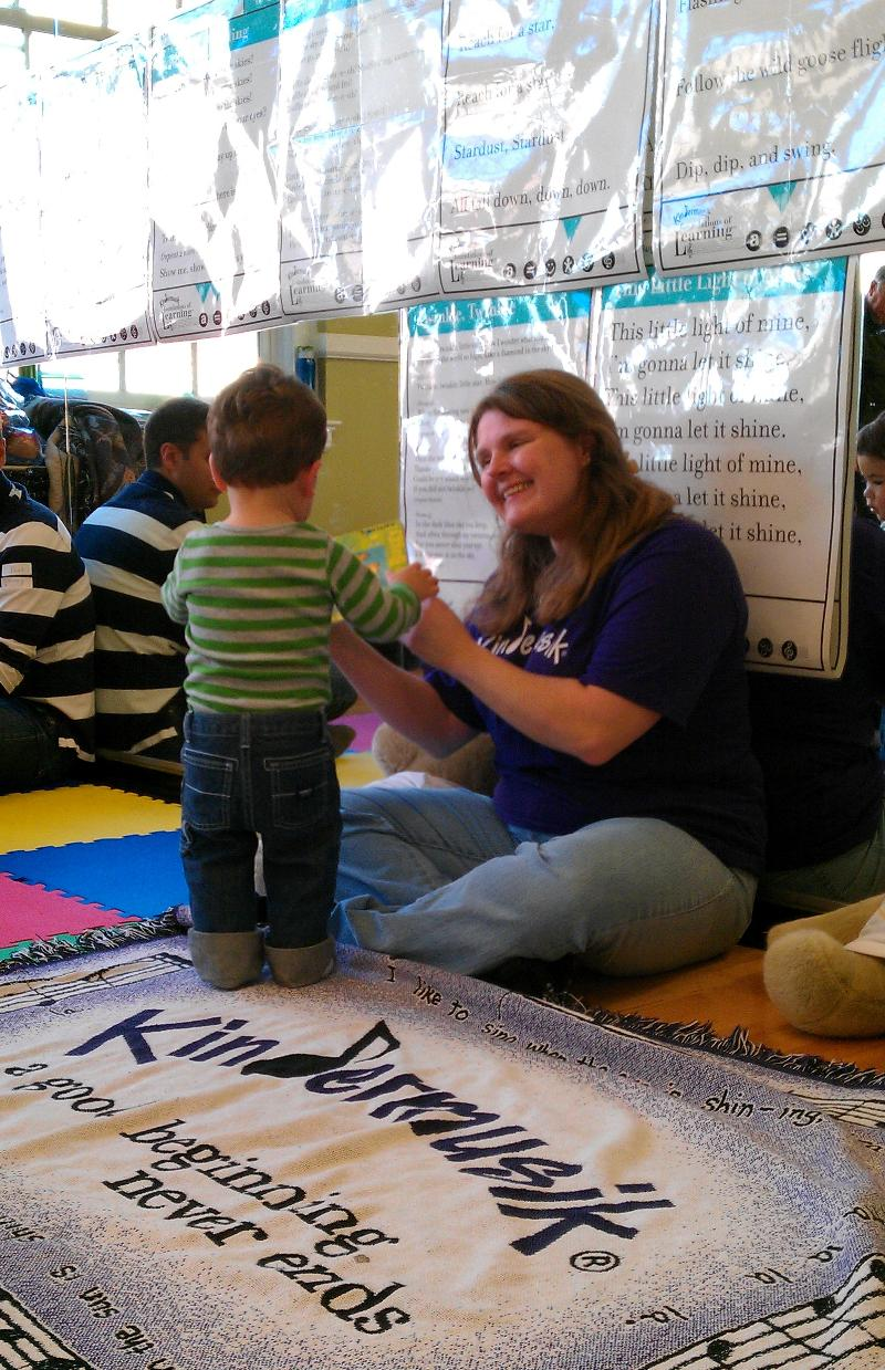 Miss Tracey at Kindermusik rug at Parent Child U
