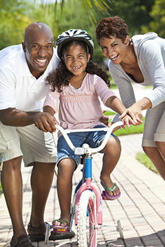 parents teaching daughter to bike