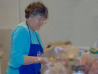 Pantry volunteer Jane Chevier repackages donated pepperoni.