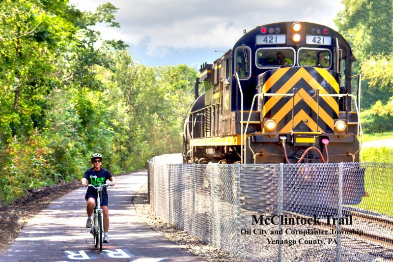 Bicyclist Debra Lutz and Train Engine on the brand new section of McClintock Trail.