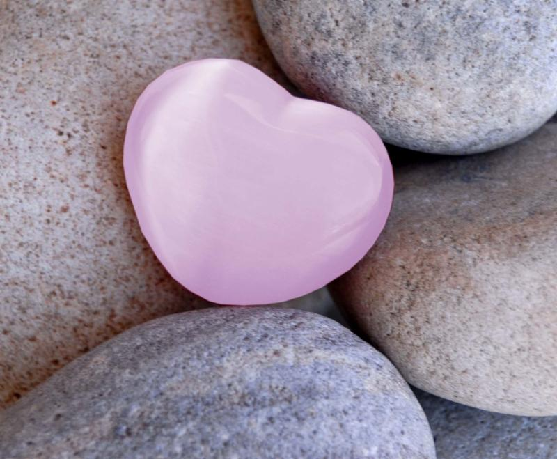 pink heart stone set in backgroung of grey stones symbol of pink represting womens health