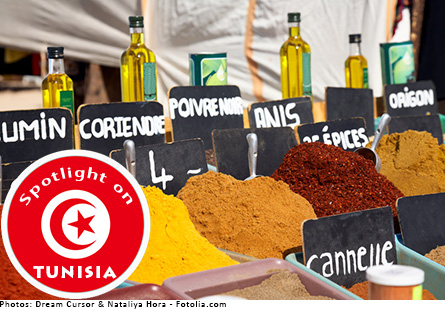 Spices in tubs at a spice market, bottles of olive oil are behind the spices. Red badge with Tunisian flag symbol of crescent moon with a star says,