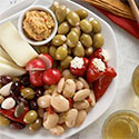 Plate with almonds, olives, stuffed peppers, cheese, and dip.