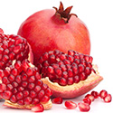 One whole pomegranate and one opened pomegranate with seeds spilling out.