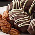 Date pecan chocolate truffles on a plate with pecans.