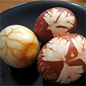 Bowl with three huevos haminados, one peeled, two in the shell.