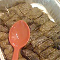 Tray of wrapped grape leaves with an orange serving spoon.