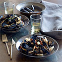 Bowls of mussels on a table set with water glasses and a linen napkin.