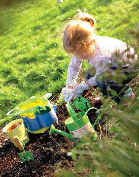 A little girl planting in a garden