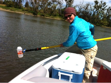 Calla Schmidt collects water samples from the Sacramento River. Credit: Norah Saarman