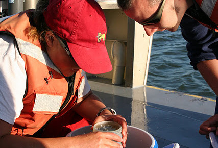 Delta Science Fellow Julien Moderan (right) collects water samples from the San Francisco Estuary.