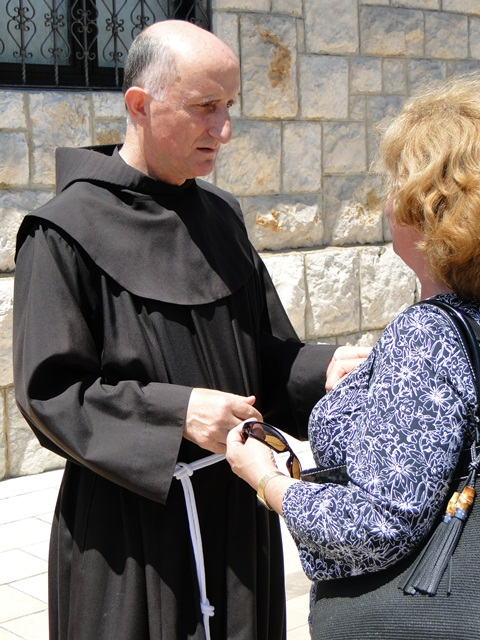 a priest comforts a widow in medj.