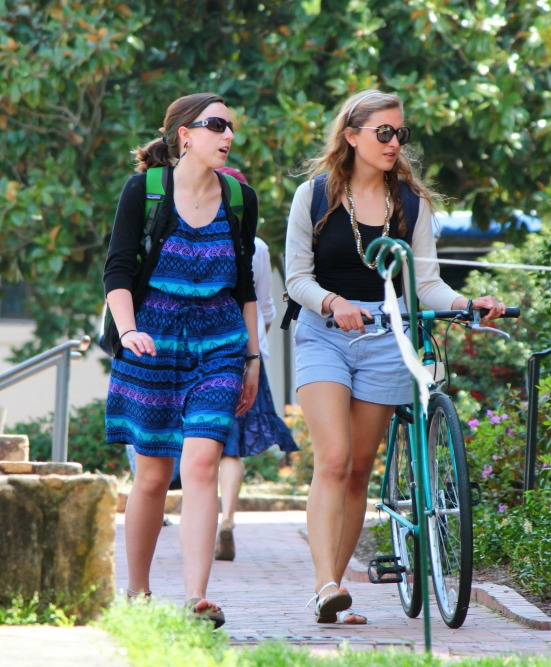 Walking with bikes on sidewalk downtown.