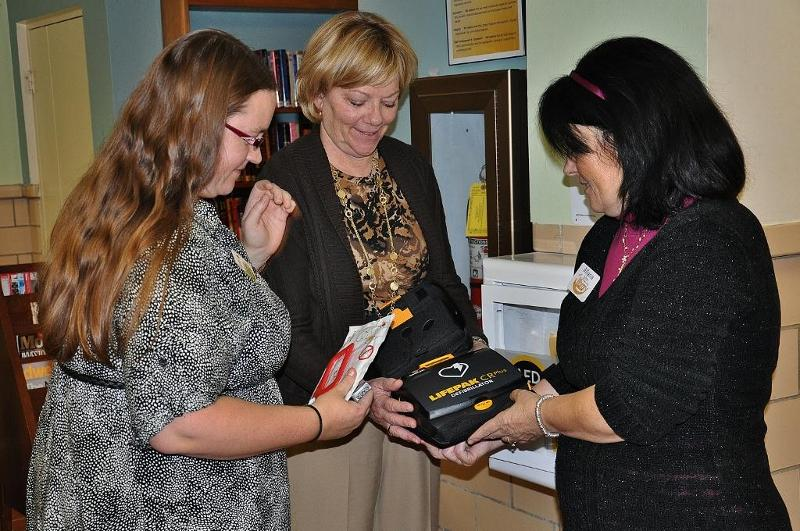 staff looking at AED equipment
