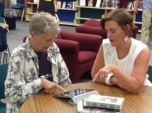 Staff assisting customer with eReader
