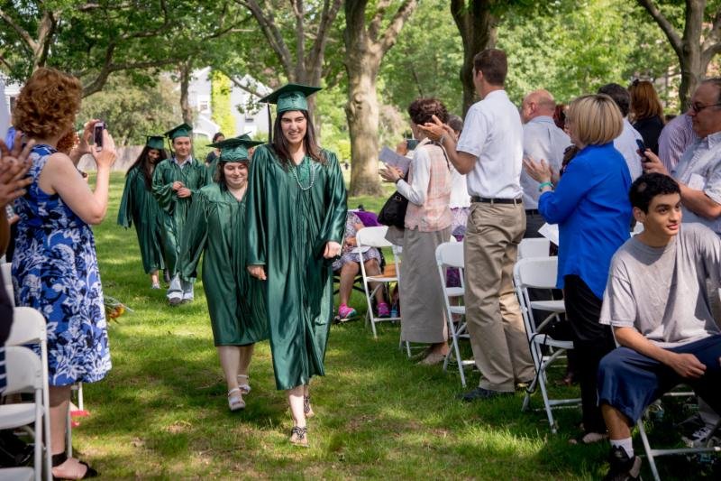 students in graduation robes and caps walk during Graduation