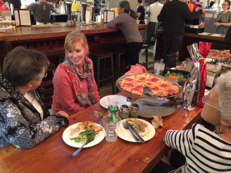 Jen chats with two volunteers over pizza and salad
