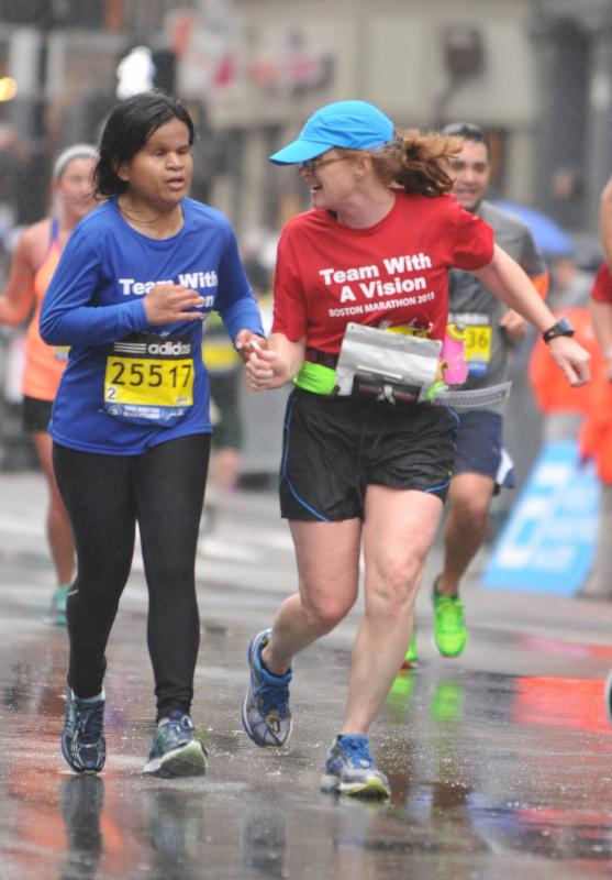 Two Team With A Vision runners - one guiding the other - run in the rain at the Boston Marathon 2015