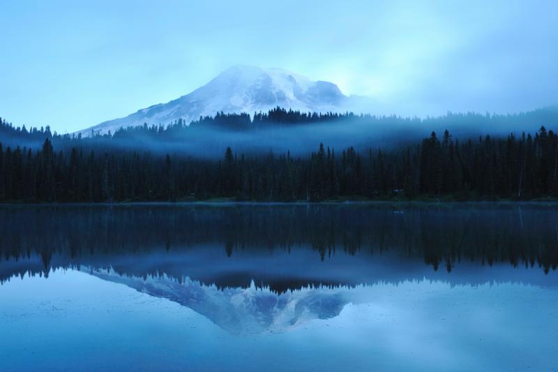 A landscape photo of a mountain surrounded by trees above a lake_ on which the landscape is reflected