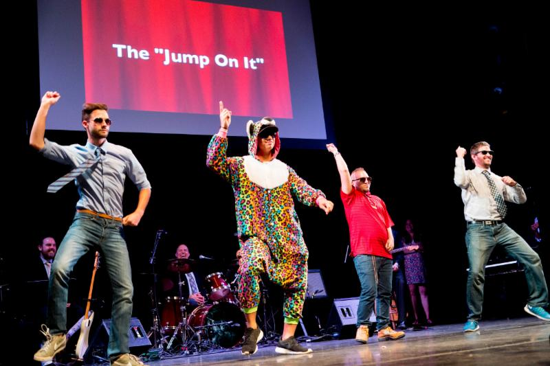 Students and staff dance on stage at Extravaganza 2015