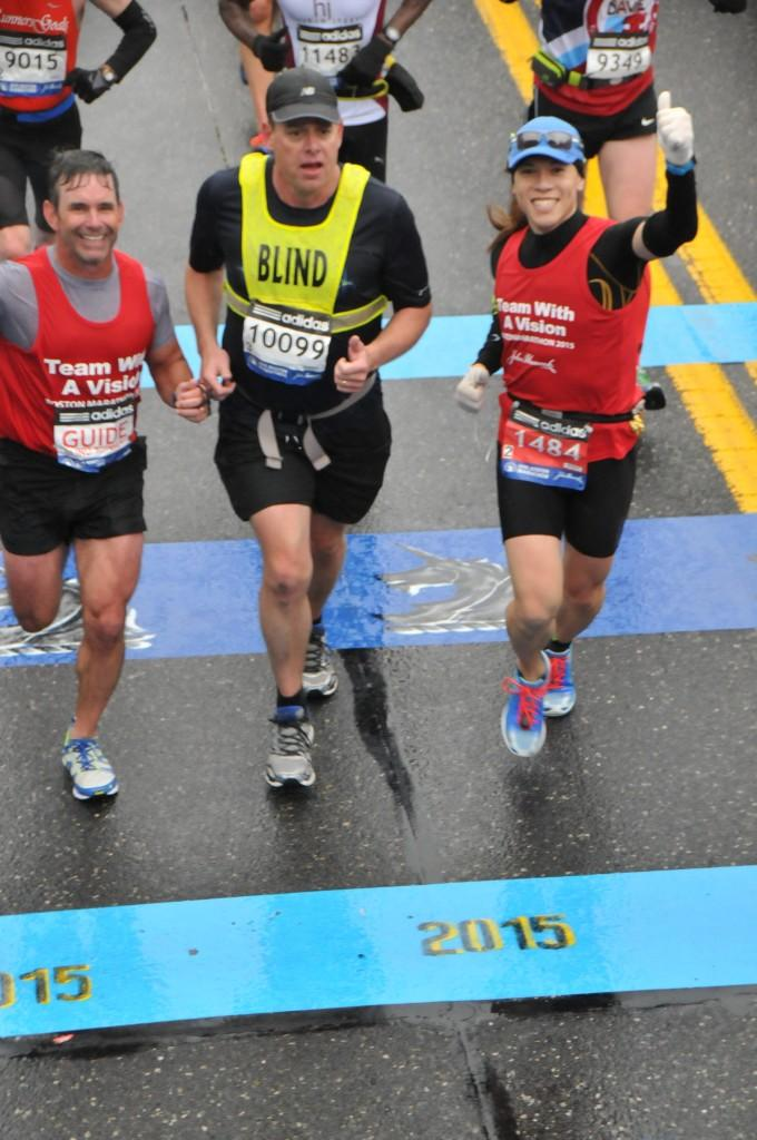 Three Team With A Vision runners crossing the Boston finish line
