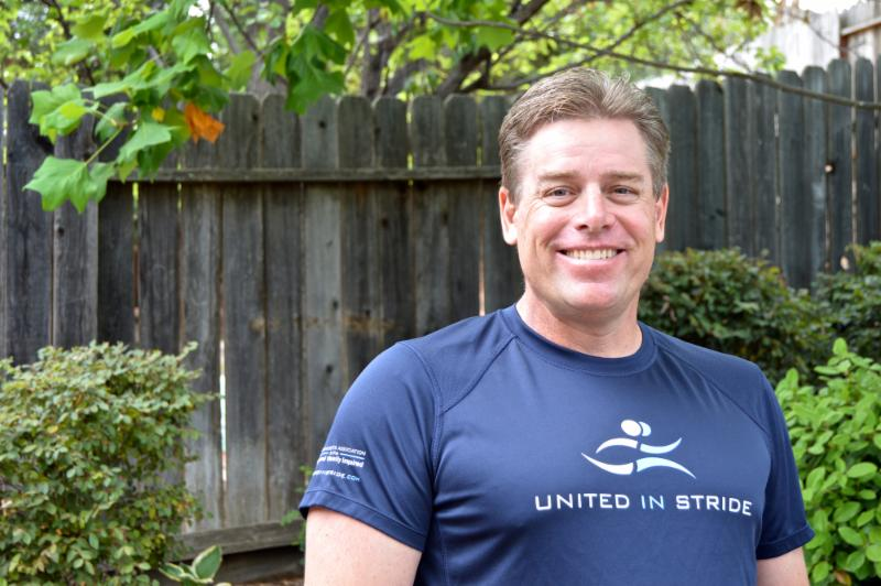 Richard Hunter smiling at the camera, wearing a United in Stride t-shirt
