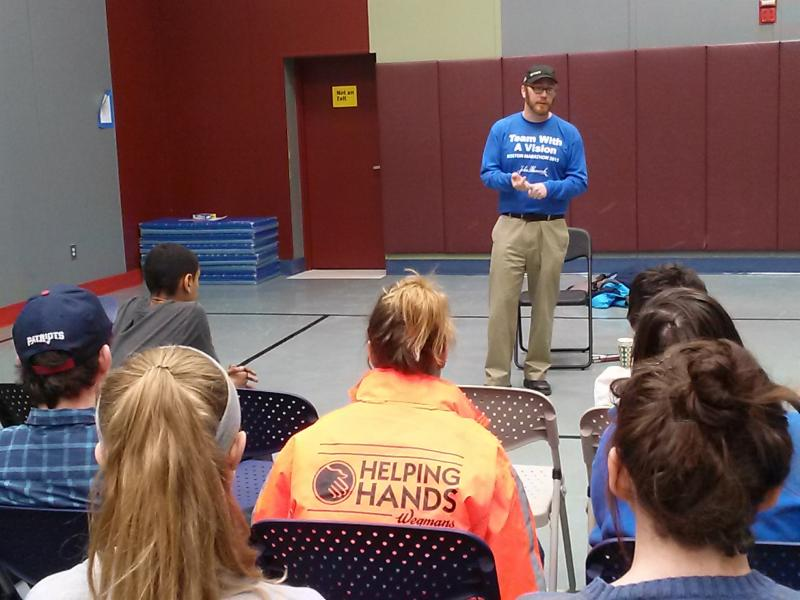 Kyle_ wearing a blue Team With A Vision shirt_ speaking to a group of students in the school gym