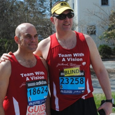 Erich Manser and his sighted guide Peter Sagal, host of Wait, Wait, Don't Tell Me, posing together before the 2014 Boston Marathon.