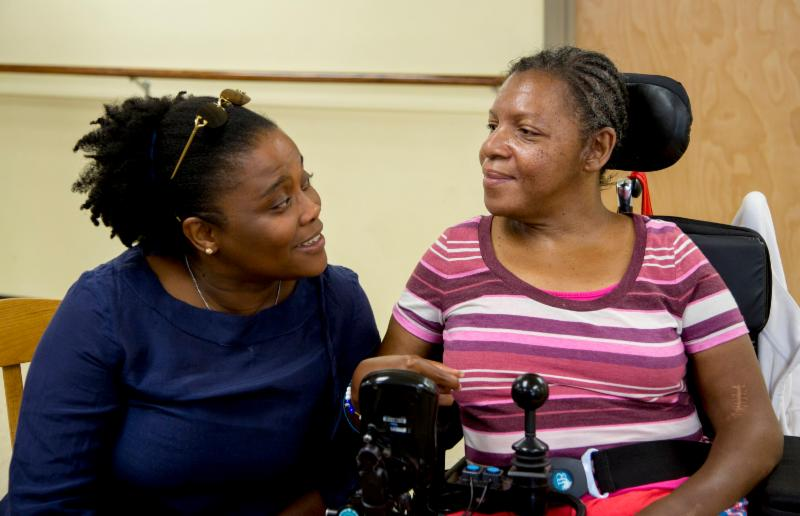 An Adult Disability Services staff talks with an individual in a wheelchair