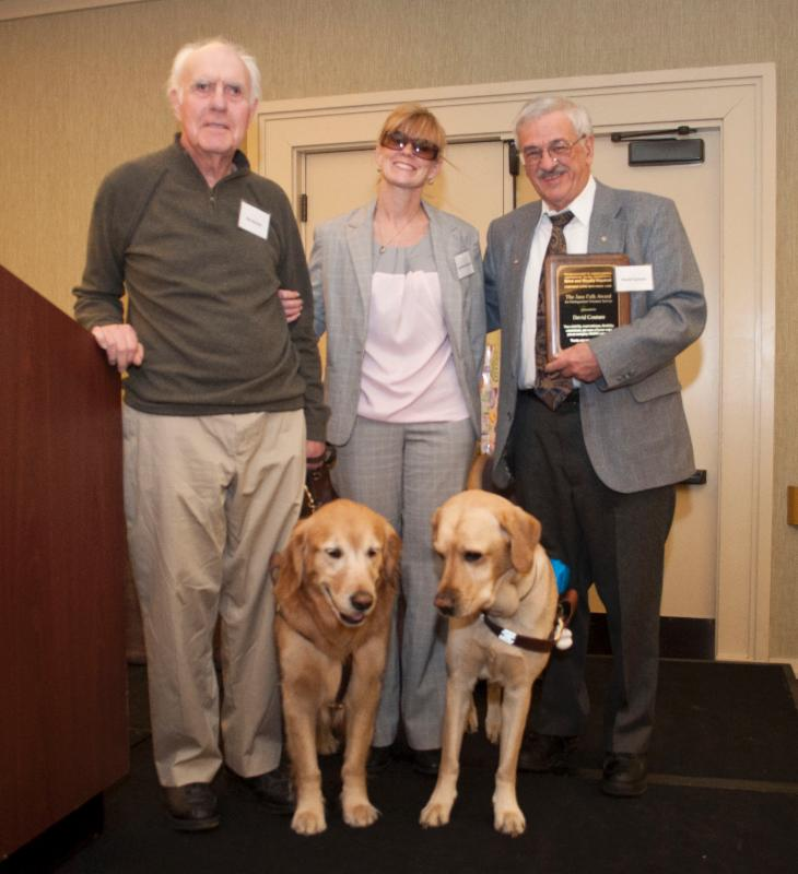 Volunteer Coordinator Jen Buchanan and her guide dog Keating present the Jane Falk Award to Dave Couture alongside Ken Bowles and his guide dog Finnegan