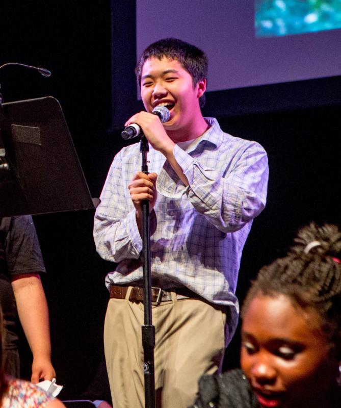 An Ivy Street School student sings into a standing microphone at Extravaganza