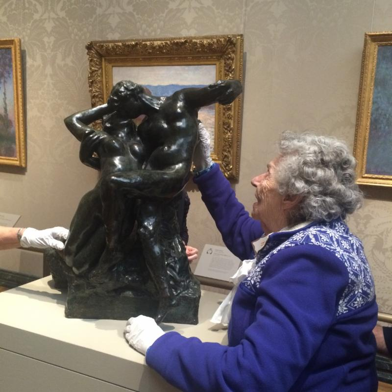 A Low Vision Peer Support Group member, wearing white gloves, investigates a sculpture at the MFA's A Feeling for Form