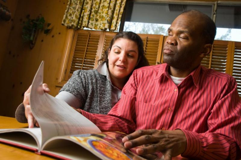 A volunteer reading to a man who is visually impaired