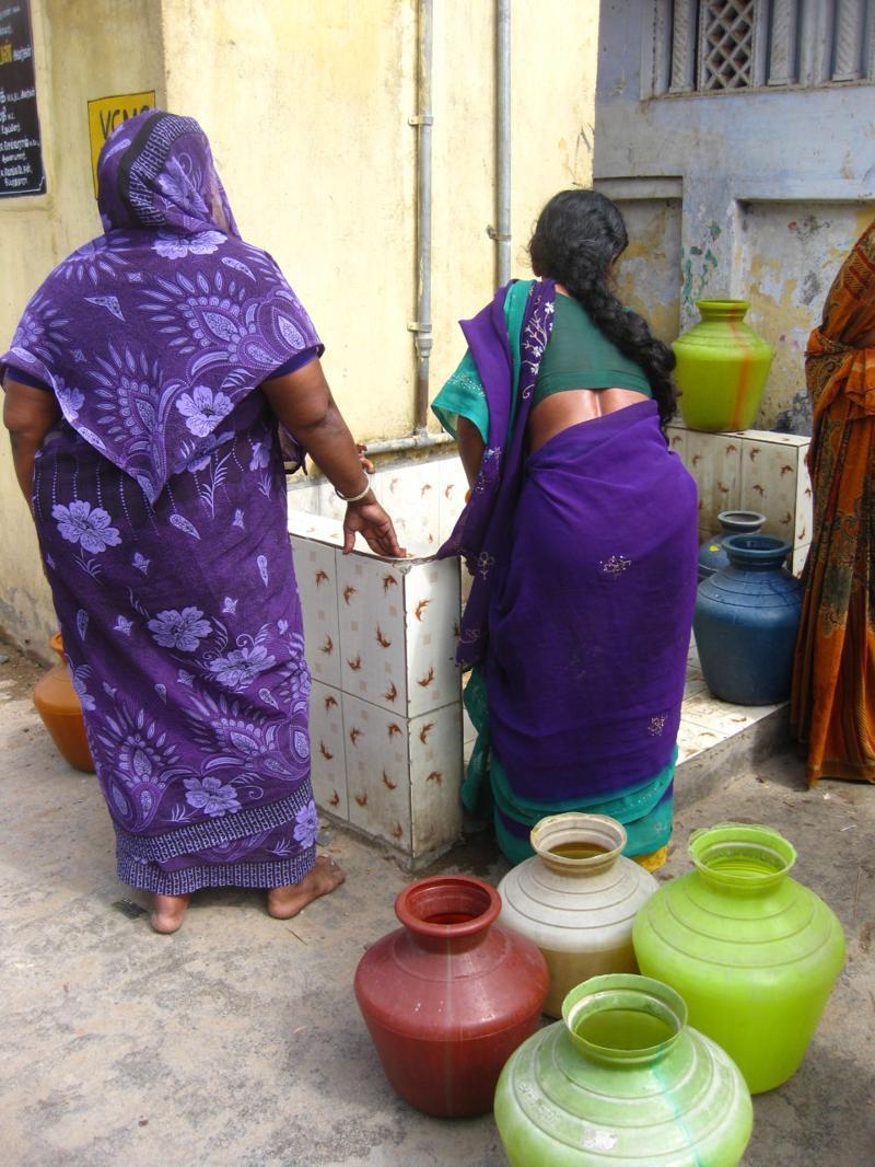 Women filling water buckets in India